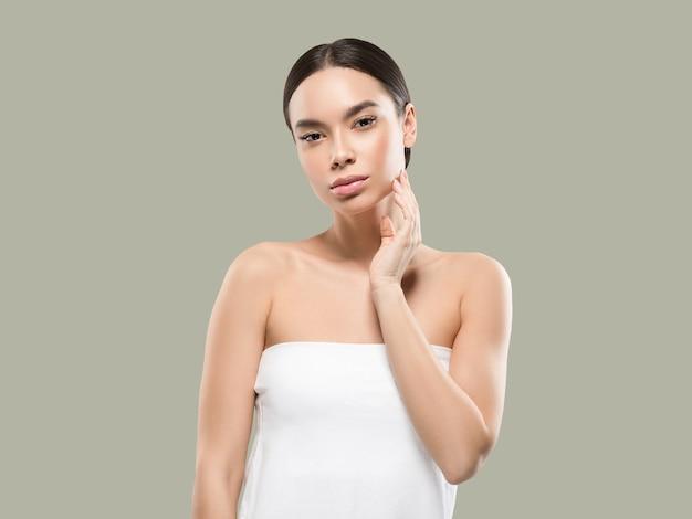 Ritratto del corpo del viso di bellezza della donna dell'asia che tocca la sua pelle sana del viso. colore di sfondo. verde