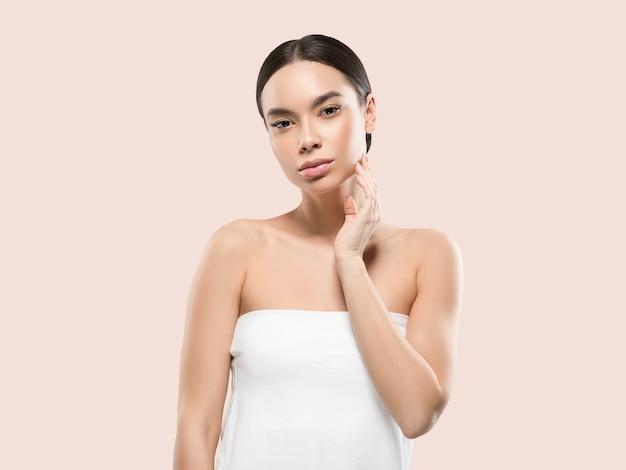 Ritratto del corpo del viso di bellezza della donna dell'asia che tocca la sua pelle sana del viso. colore di sfondo. rosa