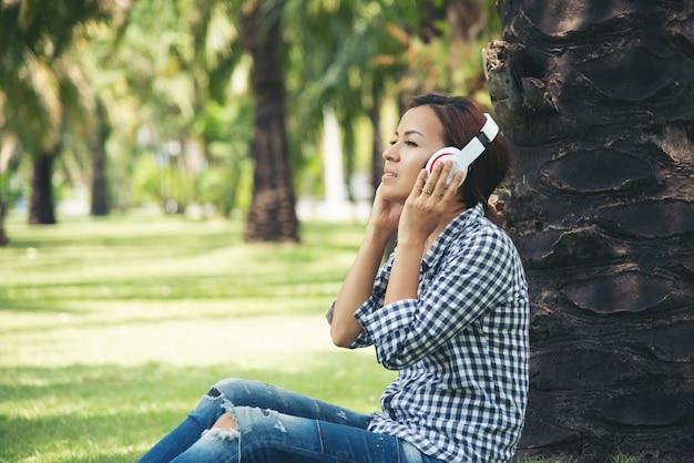 La donna dell'asia gode dell'ascolto della musica in linea sotto l'albero al parco pubblico. rilassarsi tecnologia internet del concetto di cose