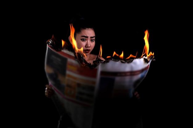 La donna asiatica tiene accesa e legge un giornale che brucia il fuoco sullo sfondo nero