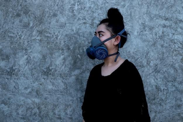 Donna asiatica che indossa un respiratore con filtro antiparticolato sostituibile a mezza maschera