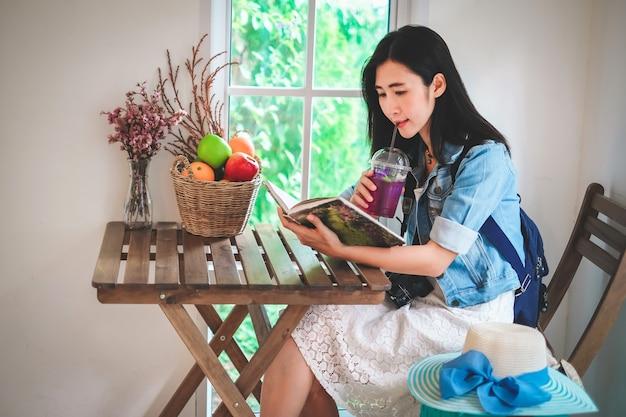 Donna dell'asia che legge un libro e che beve un succo nella caffetteria.
