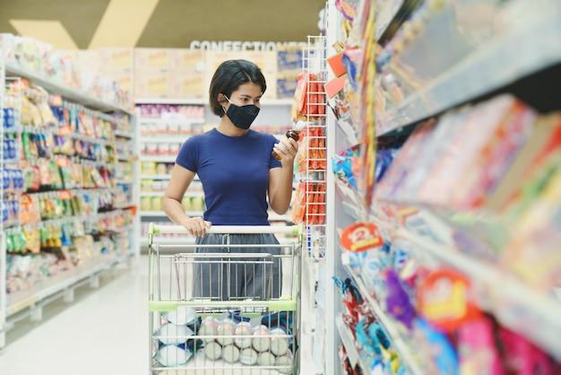 Donna asiatica che indossa una maschera che fa shopping nel grande magazzino del centro commerciale