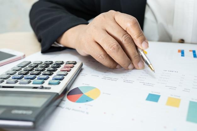 Contabile asiatico che lavora e analizza i rapporti finanziari contabilità del progetto con grafico grafico e calcolatrice in un concetto moderno di ufficio, finanza e business.