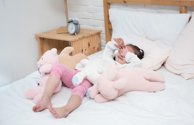 La bambina adorabile asiatica che mette su copriletto bianco osserva con la mano pigra per svegliarsi