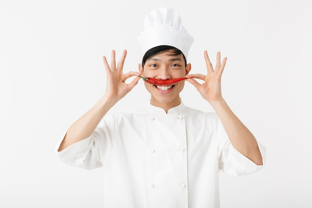 Uomo capo divertente asiatico in uniforme bianca del cuoco con peperoncino rosso sulla bocca come i baffi isolati sopra il muro bianco