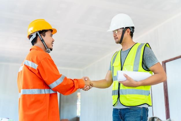Stretta di mano asiatica dell'architetto e dell'ingegnere con il caposquadra dopo aver dato istruzioni sugli appunti lavorando al cantiere