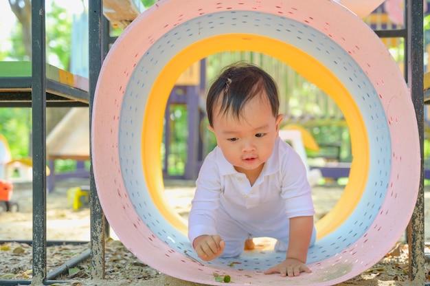 Neonato asiatico che gioca con la sabbia in una sabbiera. il bambino attivo sano all'aperto gioca il giocattolo