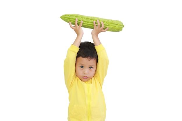 Il neonato asiatico ha sollevato la zucca amara sopra la sua testa isolata su fondo bianco
