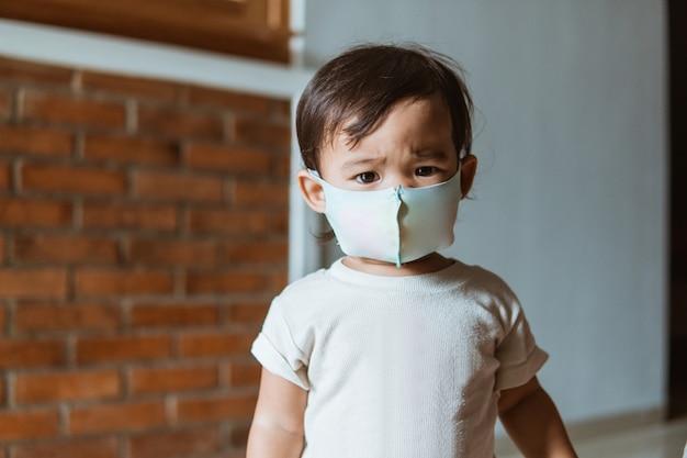Maschera da portare della neonata asiatica quando gioca a casa durante la pandemia