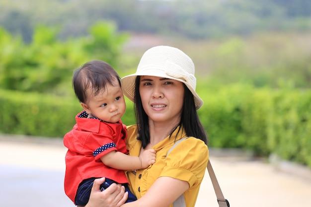 Il bambino asiatico viaggia con sua madre in vacanza.