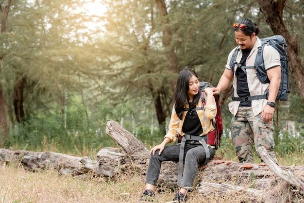 Le donne e gli uomini con lo zaino in spalla asiatici mostrano compassione l'uno per l'altro durante le escursioni, il campeggio.