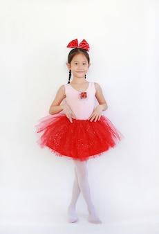 Ragazza asiatica del ballerino di balletto in gonna rosa-rossa del tutu su bianco