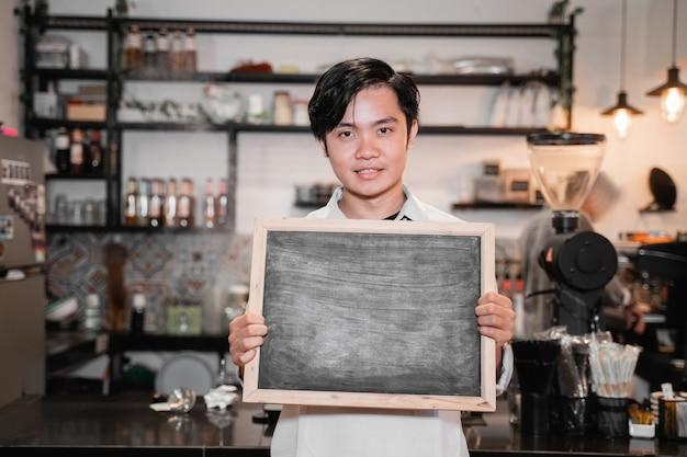 Barista asiatico in piedi e in possesso di una lavagna quando il lavoro si interrompe