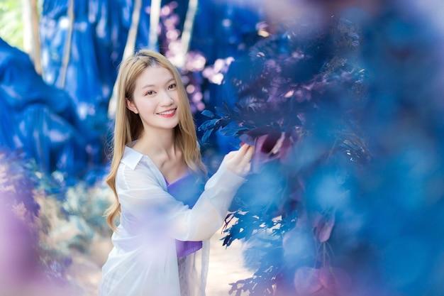 Una bella ragazza asiatica dai capelli color bronzo indossa una camicia bianca e una camicia viola sorride felicemente