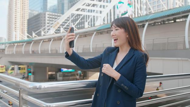 Una bella donna asiatica di affari sta effettuando la videochiamata con i colleghi o la famiglia nella città moderna, nella cooperazione commerciale e nel concetto di tecnologia aziendale.