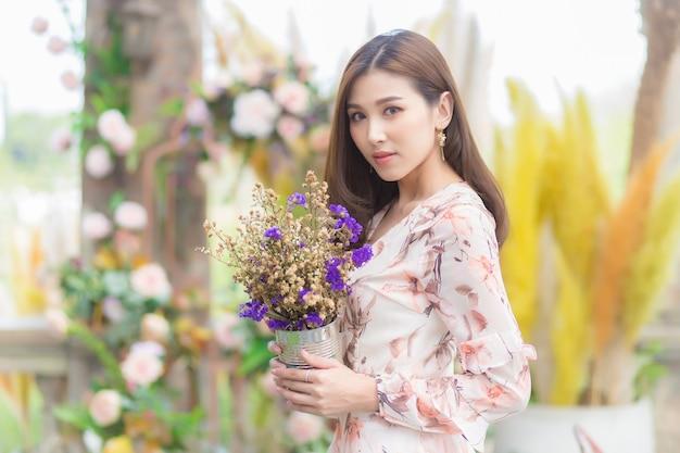 Bellissimi fiori asiatici della holding della femmina con sfondo naturale.