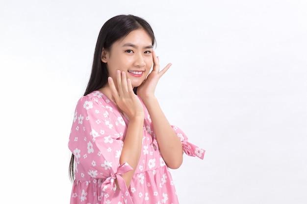 Bella donna asiatica in abito rosa e capelli lunghi neri. le sue mani toccano il sorriso sulle guance, mostrano una bella pelle su sfondo bianco.