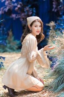 La bella femmina asiatica si siede a terra e ammira con il fiore nel giardino blu e nella foresta come sfondo.
