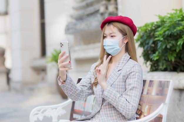 Bella donna asiatica indossa tuta e berretto rosso e tiene in mano lo smartphone per la videochiamata. fa un segno con due pollici in su che mostra la vittoria mentre si siede su una panchina nel parco all'aperto mentre indossa un medico