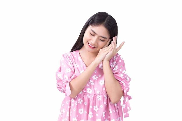 Bella ragazza asiatica in abito rosa e capelli lunghi neri le sue mani toccano la guancia e chiudono gli occhi
