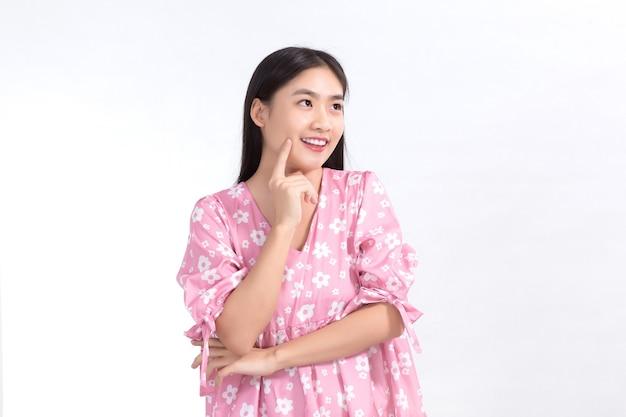 Bella ragazza asiatica in abito rosa e capelli lunghi neri. le sue mani toccano il sorriso sulle guance, mostrano una bella pelle su sfondo bianco.