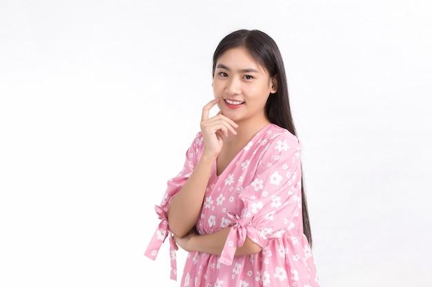 Bella ragazza asiatica in abito rosa e capelli lunghi neri le sue mani toccano la guancia, il sorriso mostra la pelle