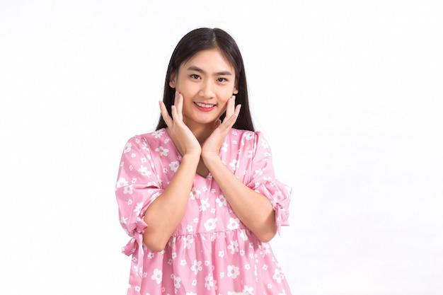 Bella ragazza asiatica in abito rosa e capelli lunghi neri le sue mani toccano il sorriso sulla guancia