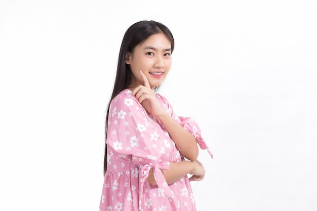 Bella ragazza asiatica in abito rosa e capelli lunghi neri le sue mani toccano la guancia smilebeautiful skin
