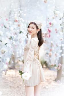 La bella ragazza asiatica che indossa un vestito color crema sorride e si trova in un giardino fiorito di rose bianche come naturale