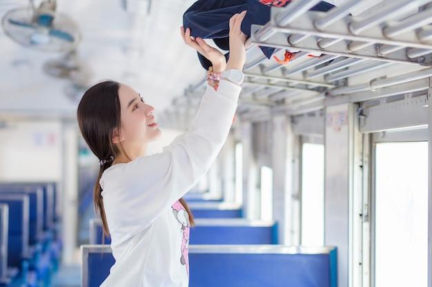 La bella ragazza asiatica in camicia bianca sta viaggiando in treno in un giorno di vacanza mentre tiene la borsa