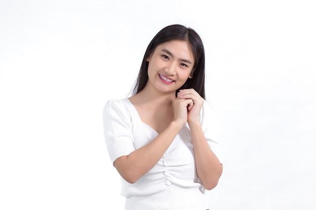 Bella ragazza asiatica che ha i capelli lunghi sorride e mostra la mano vicino al viso su sfondo bianco.