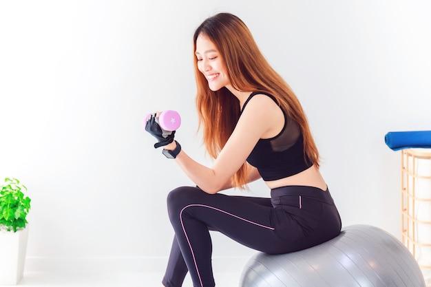 Bella donna felice asiatica che tiene un manubrio e che si siede sulla palla adatta