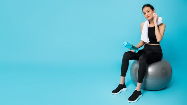 Bella donna felice asiatica che tiene la bottiglia di acqua e che si siede sulla palla adatta dopo l'esercizio isolato sull'azzurro