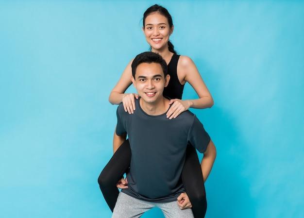 Bella donna asiatica felice che cavalca la schiena del ragazzo dopo aver esercitato isolato su sfondo di colore blu. concetto di allenamento ragazza magra e sana.
