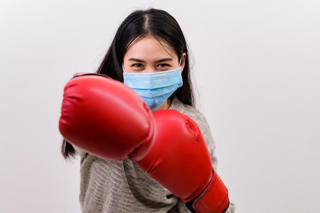 Bella giovane donna asiatica felice che indossa la protezione della maschera e guantoni da boxe lei si prepara per la lotta contro il coronavirus, con copia spazio