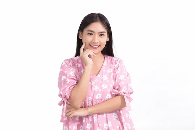 Bella signora asiatica in abito rosa e capelli lunghi neri le sue mani toccano la guancia sorridono bella pelle