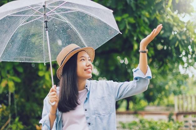 Bella donna sorridente asiatica che copre gli ombrelli sotto la pioggia con la mano che gioca goccia di pioggia nel parco