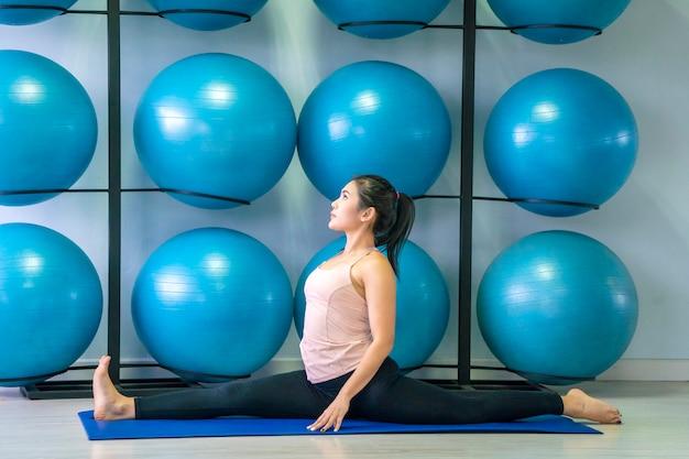 Bella donna asiatica che fa yoga nella classe di yoga