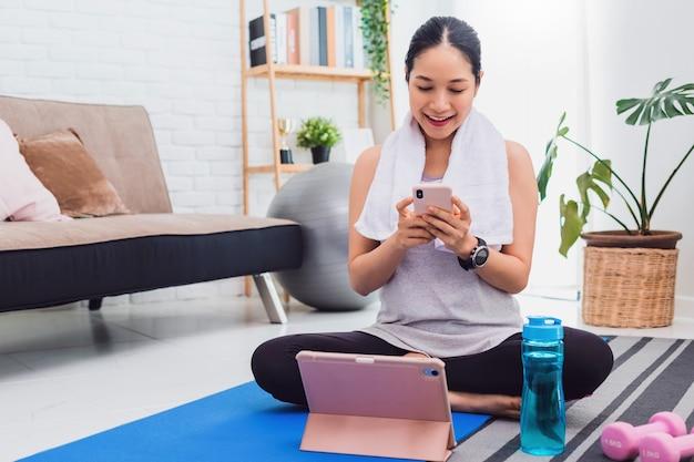 Bella donna asiatica esercizio a casa e guardare video di formazione su smartphone e tablet.