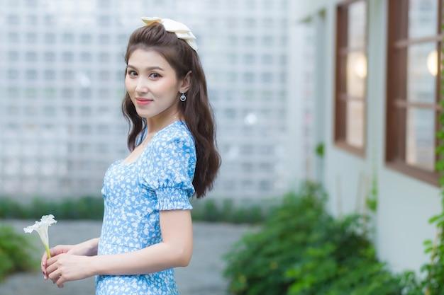 La bella donna asiatica ha i capelli castano scuro in un bel vestito blu con la margherita bianca