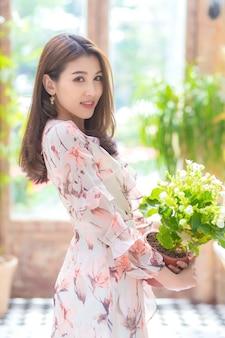 Bella donna asiatica che tiene i fiori con sfondo naturale.