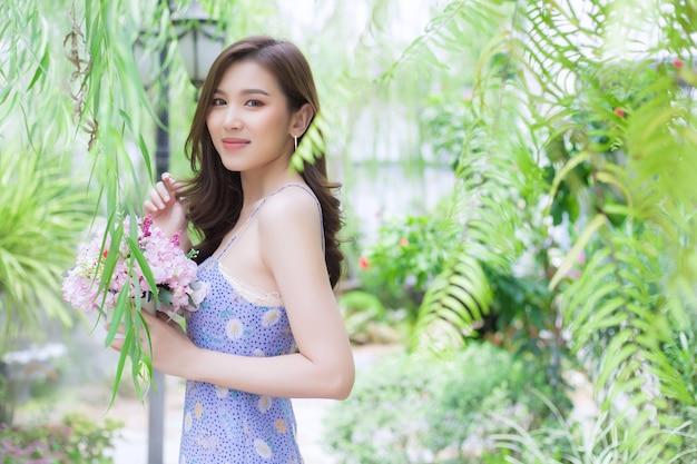 La bella donna asiatica tiene un mazzo di fiori rosa sulle sue mani e si trova in un giardino naturale verde