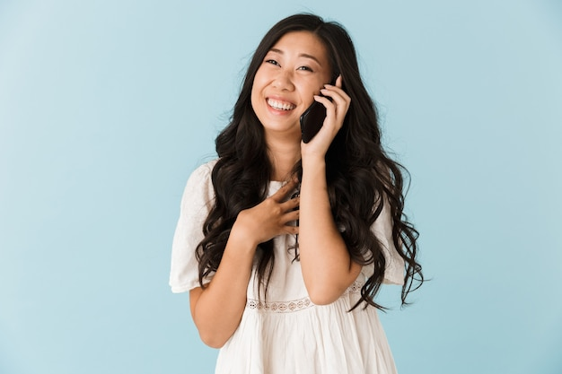 Bella donna asiatica isolata sopra la parete blu che parla dal telefono cellulare