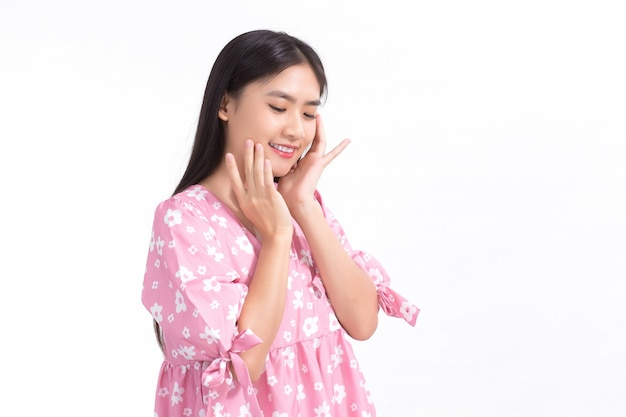 Bella donna asiatica in vestito rosa e capelli lunghi neri. le sue mani toccano il sorriso sulle guance, mostrano una bella pelle su sfondo bianco.