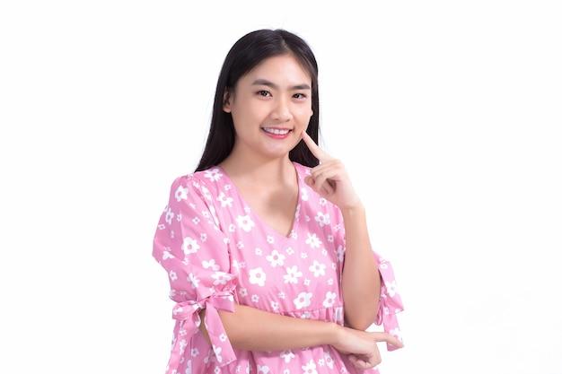 Bella donna asiatica in abito rosa e capelli lunghi neri le sue mani toccano il sorriso sulla guancia