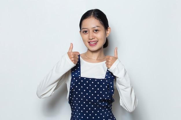 Bella donna asiatica che mostra pollice in su