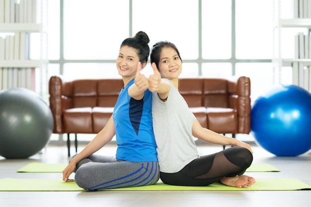 Bella donna asiatica che si siede sulla stuoia di yoga con fitball e sensazione di dolore alla caviglia