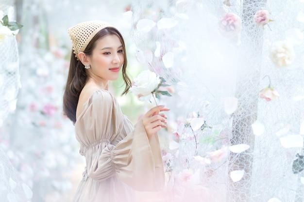La bella donna asiatica sorride e sta nel giardino fiorito della rosa bianca come tema naturale e di lusso