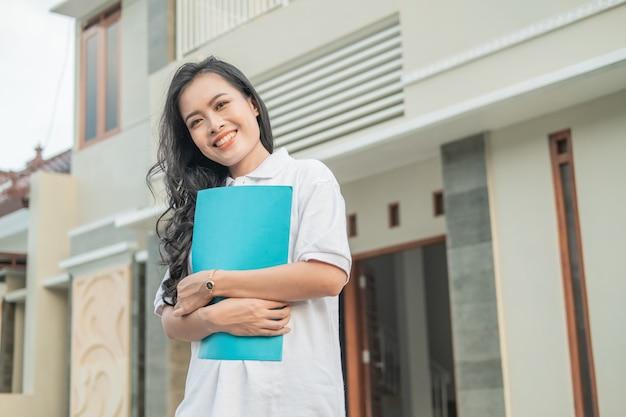 Asian bella donna in piedi tenendo il certificato di casa davanti a una nuova casa